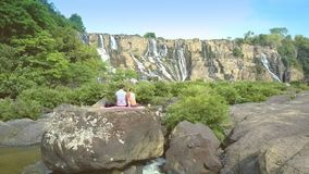 Close backside view guy girl sit on stone watch waterfall stock footage