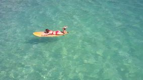 Close view girl in bikini rests on surfboard among ocean. Impressive close view slim blond girl in red bikini rests on surfboard among transparent turquoise stock video footage