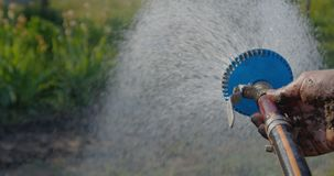 Streams of water flowing from a shower head kept by a hand in a garden in slo-mo