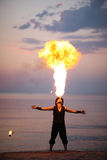 Impressive fire-breathing on the beach at sunset Stock Photography