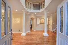 Impressive grand entry with very high ceiling and a lot of light. Impressive grand entry with very high ceiling, white columns, a lot of light and polished royalty free stock image