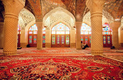 Impressive interior of Nasir ol Molk Mosque and resting people inside Stock Images