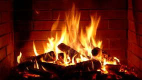 Impressive satisfying close up shot of wood burning slowly with orange fire flame in cozy brickwork fireplace atmosphere. Impressive satisfying close up shot on stock video