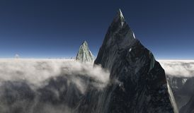 Sharp peak surrounded by low hanging clouds and a second peak in the back. An impressive sharp peak rises high above the clouds with another rocky peak standing Royalty Free Stock Photo