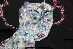 Impressive street art with face of futuristic woman`s face on black wall, Rochester, New York, 2017. Image of gorgeous street art with face of futuristic woman`s Royalty Free Stock Images