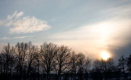 Impressive sunset in the winter with clouds and some trees in the european alps on a cold day in winter stock photos