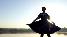 A nice woman flutters her folk dress at sunset in 4k stock video