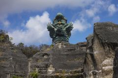 Impressive view of Garuda Wisnu green copper statue inspired in Hindu myth standing majestic under a blue sky in Indonesia travel stock photos