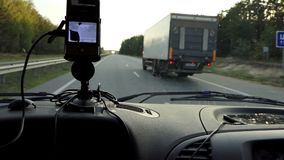 A GPS navigator on a car dashboard shows the route on a highway. An impressive view of a GPS navigator fixed on a car dashboard. It shows the route on a highway stock video footage