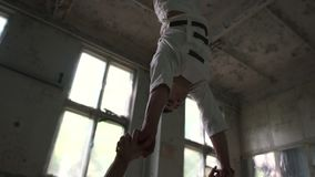 Two nut men doing acrobatic exercises and handstand on two hands in slo-mo. Impressive view of two young loony men in white uniforms doing acrobatic exercises stock footage