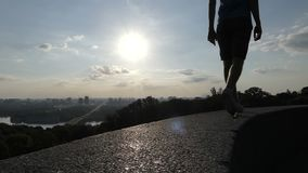 Young man walks on plates covering an embankment wall in Kyiv in slo-mo. An impressive view of a young man in shorts walking on concrete plates covering an stock footage