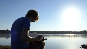 Young man looks at a family album on a lake bank in summer
