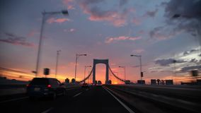 Impressive warm orange evening sunset sky over busy traffic bridge highway road from wind shield glass first person pov. Impressive warm orange evening sunset stock video footage