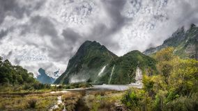 Impressive weather conditions at Milford Sound. Clouds raising and engulfing the mountain before the overnight cruise departing for Milford Sound at Fiordland Stock Images