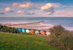 Impressive winter clouds in a cool blue sky over the beach huts and natural spit of land that stretches out to sea on the beach. In Tankerton, Whitstable, Kent stock image