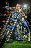 Impressive woman on a motorcycle at moto show. Beautiful fashionable brunette woman sitting on a blue motorcycle Stock Images