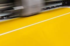 Impressora profissional grande, processando uma folha lustrosa da grande escala de rolos de papel amarelos para a amostra da cor imagens de stock royalty free