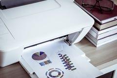 Imprimante avec des lunettes sur des livres sur la table en bois photos libres de droits