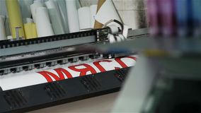 Imprimante large de format de plan rapproché avec la tête d'impression montrant le titre clips vidéos