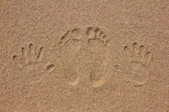 Imprint of feet and hand on the sand Royalty Free Stock Photography