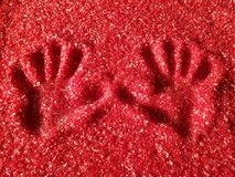 Imprint of hand. On the plastic red grains. The picture was created in the waste plastic store stock image