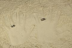 Imprint his and her palms with wedding rings. In light sand Royalty Free Stock Photos