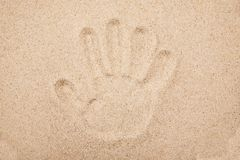Imprint of the human hand in the sand.  stock photography