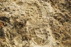 Imprint of a man`s foot. In shoes on wet sand Royalty Free Stock Photography