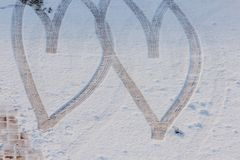 Imprint of two hearts drawn in the snow. Two hearts drawn on the snow by the wheels of a car Stock Images