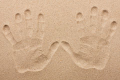 Imprint of two human hands in the sand Stock Photos
