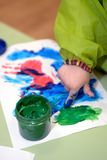 Imprint of watercolor paint on a child& x27;s hand on paper Stock Images