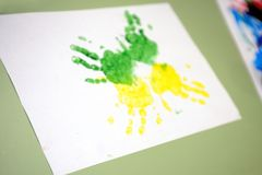 Imprint of watercolor paint on a child& x27;s hand on paper Royalty Free Stock Photography