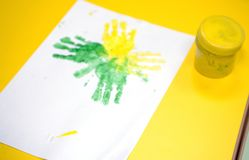 Imprint of watercolor paint on a child& x27;s hand on paper Royalty Free Stock Photos