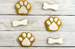 Imprints of dog`s paws and bones. Sweet cakes. White background Royalty Free Stock Photography