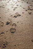 Imprints of shoe soles in the wet sand. Imprints of shoe sole profiles in the wet sand along the tide line of the Dutch North Sea beach Royalty Free Stock Images