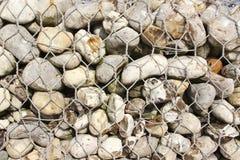 Imprisoned flint pebbles. Flintstones in a iron net Stock Image