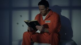 Imprisoned religious male reading bible, convicting in sins, feeling guilty stock video