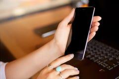 Impronta digitale femminile di esame sul suo smartphone con il computer portatile su backround La donna sblocca il telefono cellu immagine stock
