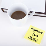 Improve your skills. Note on desk Stock Image