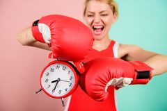Improve yourself. Overcome harmful habits. Time for training. Get used to personal regime. Girl athlete boxing gloves. And alarm clock. Sport lifestyle and royalty free stock photo