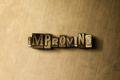 IMPROVING - close-up of grungy vintage typeset word on metal backdrop. Royalty free stock illustration.  Can be used for online banner ads and direct mail Stock Photos