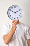 Improving his time management skills. Time running out. Close up shot of man holding clock in front of his face isolated on white background Stock Photography