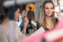 Improving the make up. Assistant improving young pretty model`s make up before session Royalty Free Stock Image