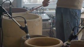 Improvisation des Schlagzeuger ` s Musikers mit hölzernen Stöcken auf großen keramischen Töpfen in der Tonwaren-Werkstatt stock video