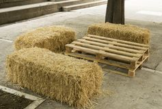 Improvisation. Table and seats with natural elements such as a pallet and straw bales Royalty Free Stock Image