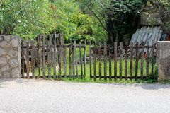 Improvised backyard fence doors made of narrow wooden boards mounted on traditional stone wall with construction material and. Garbage in yard surrounded with stock photo