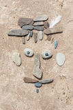 Improvised portrait of stones on the sand. The man's face made out of stones on the sand Royalty Free Stock Images