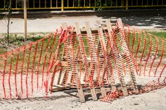 Improvised road construction site barrier with protective caution orange fence or net to protect street reconstruction work ahead.  stock photos
