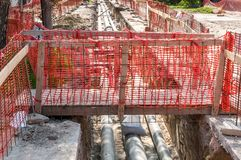 Improvised wooden bridge over the trench with new district heating pipeline system installations on the street construction site f Royalty Free Stock Image