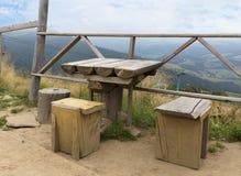 Improvisierte Restzone in Form von rauem Holztisch und Stühlen auf einen Berg in den Karpaten stockfotografie